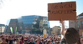 """Hunderte Menschen demonstrieren vor der Uni-Bibliothek in Freiburg. Ein Mann hält ein Pappschild mit Aufschrift """"Gegen Uploadfilter"""" hoch."""