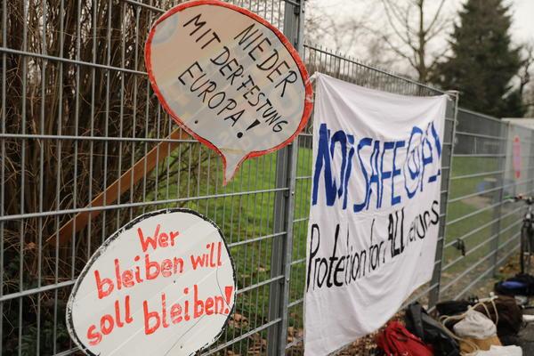 """Zwei Schilder mit """"Nieder mit der Festung Europa!"""" und """"Wer bleiben will soll bleiben!"""" sind übereinander in einen Zaun gesteckt. Daneben hängt ein Transparent: """"Not safe @ALL - Protection for ALL refugees"""""""