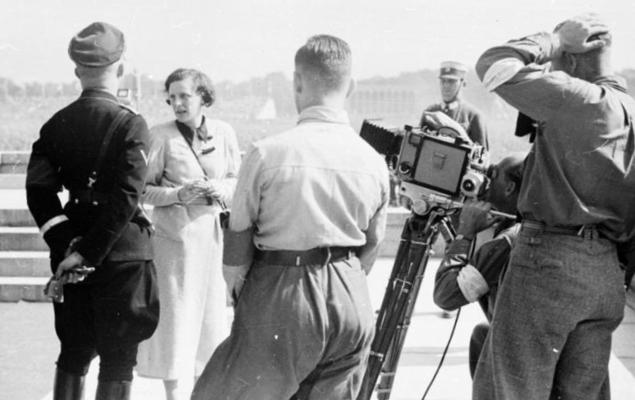 Leni Riefenstahl unterhält sich vor laufender Kamera mit Heinrich Himmler links im Bild. Rechts stehen ein dreiköpfiges männliches Kamerateam und im Hintergrund ein SA-Mitglied.