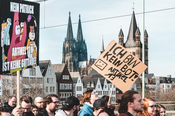 Menschen demonstrieren vor dem Hintergrund des Kölner Doms gegen Artikel 13 der EU-Urheberrechtsreform