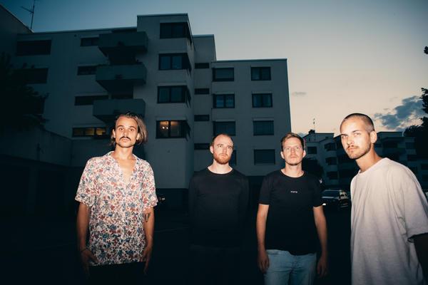 Die vier Mitglieder von Kaufmann Frust stehen bei Sonnenuntergang vor Betonhochhäusern.