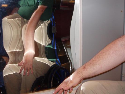 Ein Foto von einem Zerrspiegel, der ein verzerrtes Bild vom Arm einer Person im Rollstuhl zeigt.