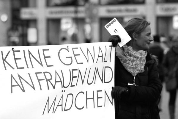Eine Frau hält ein Schild, auf dem steht: Keine Gewalt an Frauen und Mädchen