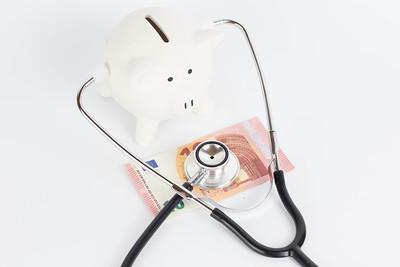 Sparschwein, das mit Stetoskop einen 10 Euro schein abhört.