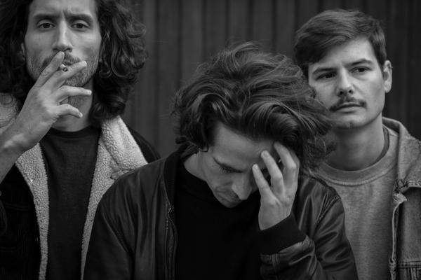 Victor, Yannick und Fidel stehen vor einer grauen Wand. Victor zieht an einer Zigarette und Yannick lehnt den Kopf in die Hand, während Fidel in die Ferne schaut.