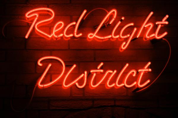 """Eine rote Neonbeleuchtung bildet den Text """"Red Light District"""""""