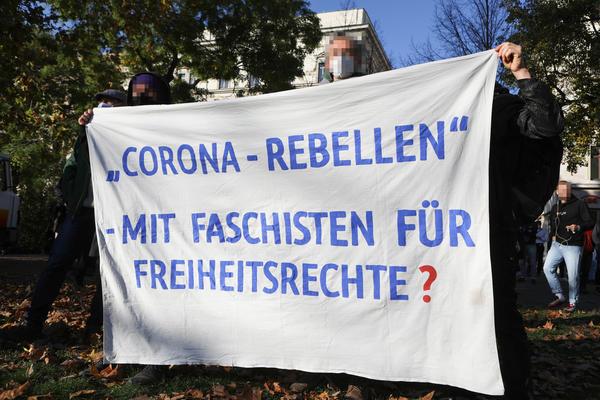 """Ein weißes Transparent wird gehalten, auf dem mit blauer Schrift steht: """"Corona-Rebellen - Mit Faschisten für Freiheitsrechte?"""""""