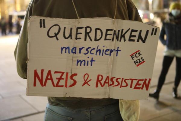 """Ein Schild auf dem steht: """"'Querdenken'"""" marschiert mit Nazis & Rassisten""""."""