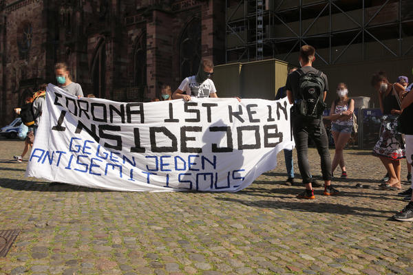 """Drei Personen halten ein Transparent auf dem steht: """"Corona ist kein Inside Job - Gegen jeden Antisemitismus"""" Davor und daneben stehen Gegendemonstrant:innen und andere und diskutieren."""
