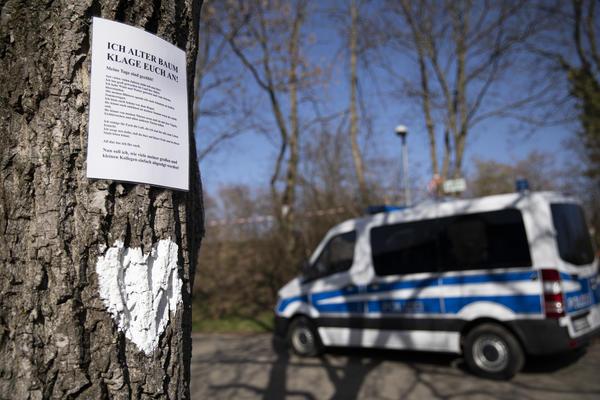 Im Vordergrund: Ein Baumstamm, an dem ein weißes Herz gemalt ist und ein Bild mit einem Gedicht hängt. Im Hintergrund eine Polizei-Wanne und ein mit Flatterband abgesperrter Bereich.