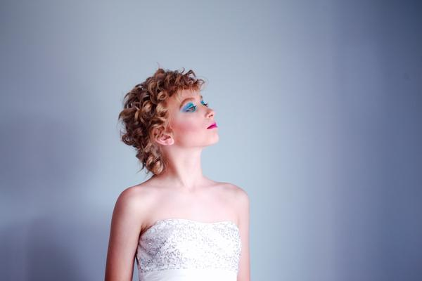 Das 10-jährige, nicht geschlechtskonforme (gender non-cornforming) Kind Bink posiert mit lockigen Haaren, blauem Lidschatten, pinkem Lippenstift, viel Selbstbewusstsein und einem glitzernd weißen Kleid vor einem grauen Hintergrund.