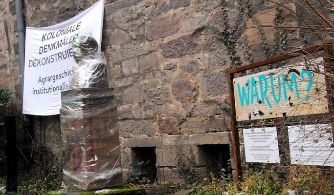 Mit Plastikfolie umwickelte Büste mit Erläuterungstafel