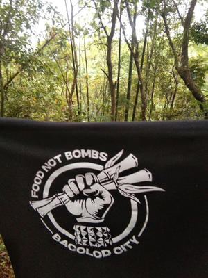 """Banner """"Food not Bombs - Bacolod City"""", im Hintergrund Wald"""