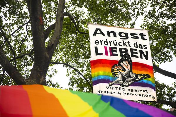 Hinter einem regenbogenfarbenen Pavillondach hängt ein senkrechtes Transparent in den Bäumen auf dem steht: Angst erdrückt das Lieben - united against trans* & homophobia.