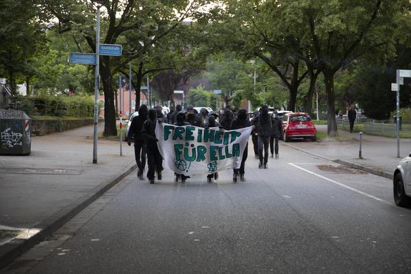 """Eine Demofront mit weißem Transparent, auf dem in grünen Buchstaben """"Freiheit für Ella"""" steht."""