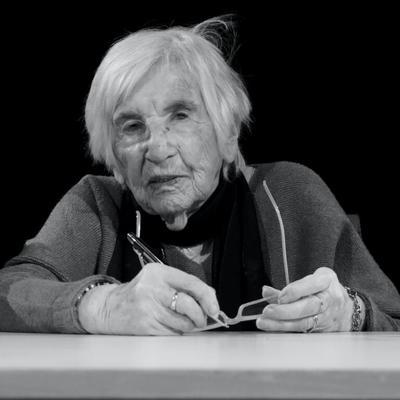 Ein Portraitfoto auf dem Esther Bejarano zu sehen ist. Sie Sitztz an einem Tisch und hat einen Kugelschreiber in ihrer rechten Hand.