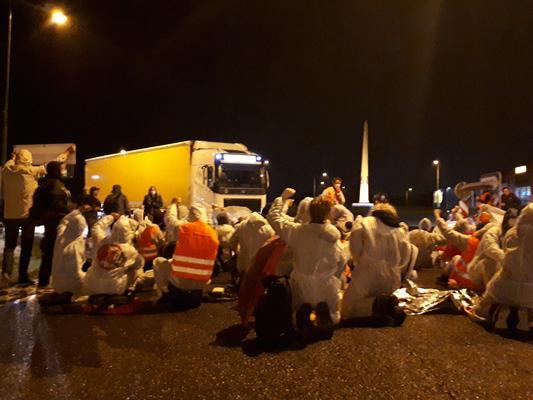 Eine Gruppe von Aktivist:innen sitzt und blockiert in weißen Malereianzügen in der Nacht, vor einem LKW.