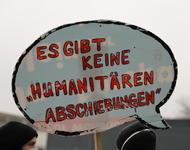 """Sprechblasen-Schild mit der Aufschrift: """"Es gibt keine 'humanitäre Abschiebungen'"""""""