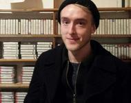 Portrait von Tobias Gralke mit schwarzer Mütze und schwarzem Pullover vor einem Kassettenregal