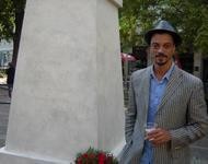 """Künstler Philip Metz neben dem Denkmal Le Héros Invisible. Auf dem Denkmal steht: """"Zu Ehren der für das deutsche Vaterland gefallenen kameruner Soldaten – 1914-1918"""""""