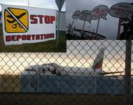 Hintergrund: Abgeschobene steigen unter Polizeibegleitung im Flugzeug der Bulgaria Air am 09.12.2014; Vordergrund: Transparente des Protests vor dem Terminal