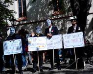 Attac-Mitglieder demonstrieren als Finanzhai, Merkel, Gabriel und Juncker verkleidet gegen TTIP.
