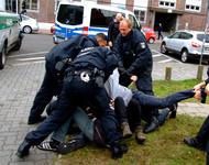 Mehrere deutsche Polizisten, die gewaltsam gegen Protestierende vorgehen, die auf dem Boden liegen.