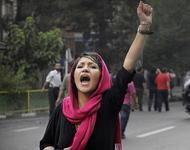 Proteste im Iran - Kopftuchtragende Demontrantin mit erhobener Faust