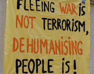 "Banner: ""Fleeing War is not Terrorism, dehumanising people is!"""