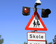 Bild von einem Schulweg Kreuzt Warnschild und Warnleuchten daneben.