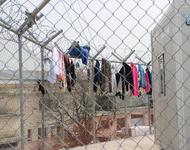 Kleider hängen zum trocknen an einem Gitter mit Stacheldraht um das Lager Vial