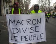 Demonstranten halten ein Transparent mit der Aufschrift 'Macron spaltet das Volk'
