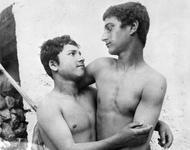 Das Bild zeigt zwei junge, sich umarmende Männer.