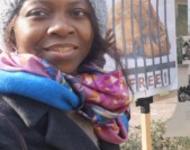 """Millicent Adjei vor einem Schild mit der Aufschrift """"Set them free"""""""