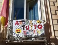 """Banner mit der Aufschrift """"Andra tutto bene"""" an einem Balkon in Italine."""