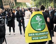 Ein Mensch läuft auf einer Demonstration mit einem Schild: Gerechte1komma5 - Der Klimaplan von unten