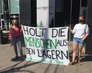 """Zwei Frauen halten ein Transparent mit der Aufschrift """"Holt die Menschen aus den Lagern"""" hoch. Sie tragen Mundschutz."""
