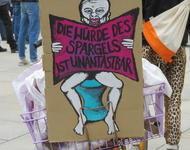 """Plakat mit """"Die Würde des Spargels ist Unantastbar"""" und einem Menschen auf einer Kloschüssel"""