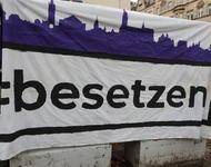 """Ein Banner, auf dem """"#besetzen"""" steht und eine Stadtsilhouette in violett gemalen ist."""