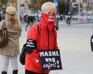 """Eine Frau in roter Jacke trägt eine rote Maske, auf der """"unter Zwang"""" steht, eine schwarze Armbinde, auf der """"Ich denke selber!"""" steht und ein Schuld um den Hals gebunden hat, auf dem """"Maske weg, sorort!"""" steht."""