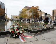 Ein Blumenkranz liegt vor dem Gedenkbrunnen der Alten Synagoge. An dessen Rand sind Blumen abgelegt.