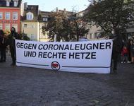 """Weißes Transparent, auf dem in schwarzer Schrift steht: """"Gegen Coronaleugner und rechte Hetze"""". Außerdem Antifa-Symbol."""