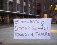 """Ein weißes Transparent auf dem Platz der Alten Synagoge, auf dem steht: """"25. November - Stopp Gewalt an Frauen"""". Ergänzt durch das Frauensymbol in der rechtsobigen Ecke und Handabrücke auf der Unterseite."""