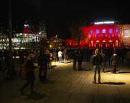 Das Freiburger Stadttheater rot beleuchtet, im Dunkeln, Auf dem Platz davor verteilt stehen Menschen mit Instrumenten.