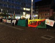 """Reihe von Demontrant*innen, die Transparente halten, auf denen unter anderem """"Defend Afrin"""" und """"Fight for Rojava"""" steht."""