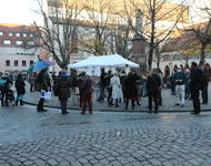 Eine Gruppe von Menschen sammelt sich um einen weißen Pavillion.