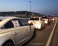 """Eine Reihe von Autos, an dem vordersten hängt an dem Seitenfenster ein Schild mit der Aufschrift """"Impfen kann töten""""."""