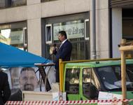 Mandic hetzt auf dem Lörracher Marktplatz. Im Hintergrund sieht man die Logos von der Badischen Zeigung und Dem Sonntag, in der Schaufensterscheibe.