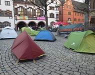 """Ein paar Zelte stehen vor einem """"Seebrücke jetzt!""""-Transparent auf dem Freiburger Rathausplatz. Im Hintergrund sieht man Menschen, einen Pavillion und das Alte Rathausgebäude."""