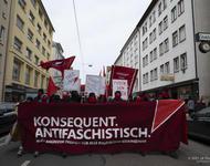 Demonstrationsfront mit rotem Transparent auf dem in weißen Großbuchstaben steht: Konsequent antifaschistisch.